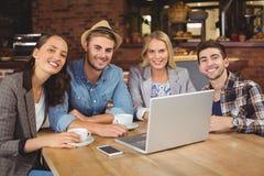 Lächelnde Freunde, die Kaffee sitzen und trinken stockfotografie