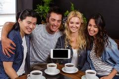 Lächelnde Freunde, die Kaffee und das Nehmen von selfie genießen Stockfotos