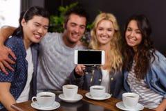 Lächelnde Freunde, die Kaffee und das Nehmen von selfie genießen Stockbild