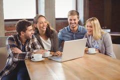 Lächelnde Freunde, die Kaffee und die Anwendung des Laptops trinken Stockfoto
