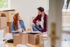 Lächelnde Freunde, die Material auspacken und Kaffee im Innenraum mit Kästen trinken lizenzfreie stockfotos