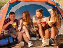 Lächelnde Freunde, die Schnellimbissnudeln auf einem Camping-Ausflug essen Wanderer, die auf einem Zelthintergrund essen Aktives  lizenzfreie stockfotografie