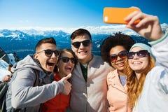 Lächelnde Freunde, die selfie mit Smartphone nehmen lizenzfreie stockfotografie