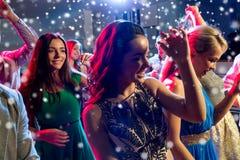 Lächelnde Freunde, die in Verein tanzen stockfotografie