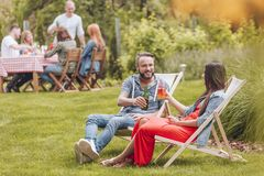 Lächelnde Freunde, die während der Sitzung bei der Entspannung auf sunbeds im Garten zujubeln stockfoto