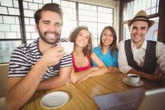 Lächelnde Freunde, die zusammen Kaffee genießen Stockfotos