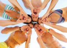 Lächelnde Freunde im Kreis auf Sommerstrand Lizenzfreie Stockbilder