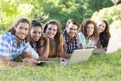 Lächelnde Freunde im Park unter Verwendung des Tabletten-PC und -laptops Stockfoto