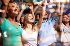 Lächelnde Freunde am Konzert im Verein Stockbild