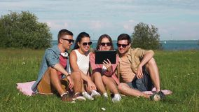 Lächelnde Freunde mit dem Tabletten-PC, der auf Gras sitzt stock video