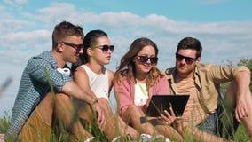 Lächelnde Freunde mit dem Tabletten-PC, der auf Gras sitzt stock video footage