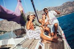 Lächelnde Freunde mit Gläsern Champagner auf Yacht lizenzfreie stockfotografie