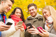 Lächelnde Freunde mit Smartphones im Herbstpark Stockfotos