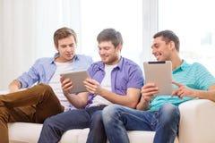 Lächelnde Freunde mit Tabletten-PC-Computern zu Hause Lizenzfreies Stockfoto