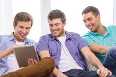 Lächelnde Freunde mit Tabletten-PC-Computern zu Hause Lizenzfreies Stockbild