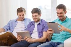 Lächelnde Freunde mit Tabletten-PC-Computern zu Hause Lizenzfreie Stockfotos