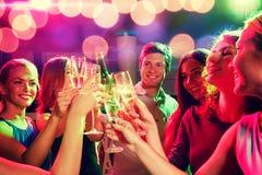 Lächelnde Freunde mit Weingläsern und -bier im Verein stockfotografie