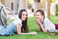 lächelnde Freundinnen, die auf Gras mit Fahrrad und Skateboard legen lizenzfreies stockfoto