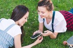lächelnde Freundinnen, die auf Gras mit Smartphone und Skateboard legen lizenzfreies stockfoto