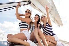 Lächelnde Freundinnen, die auf Yachtplattform sitzen Stockfoto