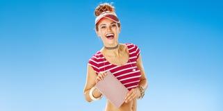 Lächelnde geeignete Frau in der roten Sonnenblende auf dem Strand, der Buch zeigt Lizenzfreies Stockfoto