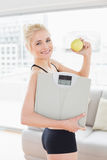 Lächelnde geeignete Frau in der Sportkleidungsholding stufen und Apfel ein Stockfoto