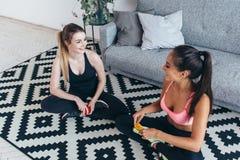 Lächelnde geeignete Frauen, welche die Sportkleidung sitzt auf dem Boden isst Früchte und die Unterhaltung tragen lizenzfreies stockbild