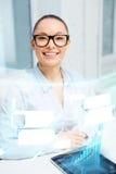 Lächelnde Geschäftsfrau in den Brillen mit Tabletten-PC Stockfoto