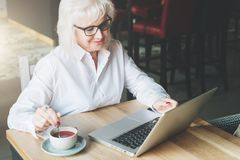 Lächelnde Geschäftsfrau in den Gläsern, die bei Tisch, arbeitend auf La sitzen Stockbilder