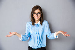 Lächelnde Geschäftsfrau in der Geste des Fragens über grauem Hintergrund Lizenzfreies Stockbild