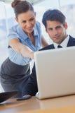 Lächelnde Geschäftsfrau, die auf den Laptop zeigt Stockfotografie