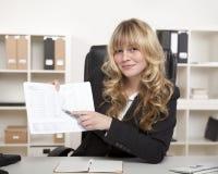 Lächelnde Geschäftsfrau, die auf eine Tabelle zeigt Stockfoto