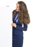 Lächelnde Geschäftsfrau, die auf leerer Anschlagtafel schaut Stockbild