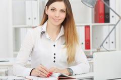Lächelnde Geschäftsfrau, die am Büroarbeitsplatz in camera schaut sitzt Stockfotos