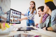 Lächelnde Geschäftsfrau, die den Mitarbeitern Bildschirm zeigt lizenzfreie stockbilder