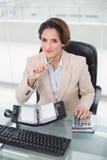 Lächelnde Geschäftsfrau, die den Taschenrechner und Tagebuch betrachten Kamera verwendet Stockbild