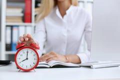 Lächelnde Geschäftsfrau, die in der Hand Uhr hält Stockbilder