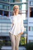 Lächelnde Geschäftsfrau, die draußen mit Handy geht Stockbild