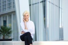 Lächelnde Geschäftsfrau, die draußen mit Handy sitzt Stockbild