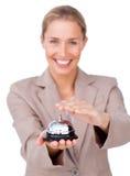 Lächelnde Geschäftsfrau, die eine Service-Glocke anhält Stockbild
