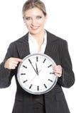 Lächelnde Geschäftsfrau, die eine Uhr hält Stockfotos