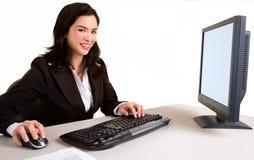 Lächelnde Geschäftsfrau, die an einem Computer arbeitet Stockfotografie