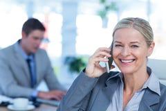 Lächelnde Geschäftsfrau, die einen Telefonanruf mit Kollegen im Hintergrund hat Stockfotos