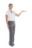 Lächelnde Geschäftsfrau, die etwas mit ihrer Hand darstellt Stockfoto