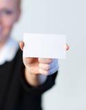 Lächelnde Geschäftsfrau, die heraus eine Visitenkarte anhält Stockfoto