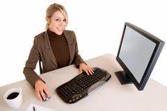 Lächelnde Geschäftsfrau, die an ihrem Computer arbeitet Stockfotografie