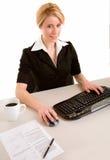 Lächelnde Geschäftsfrau, die an ihrem Computer arbeitet Stockbilder