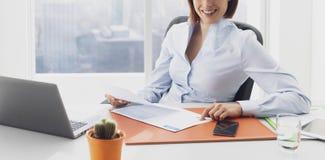 Lächelnde Geschäftsfrau, die im Büro und in der Prüfung von Diagrammen arbeitet lizenzfreie stockbilder