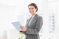 Lächelnde Geschäftsfrau, die Kamera und die Anwendung ihrer Tablette betrachtet Lizenzfreie Stockfotos