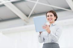 Lächelnde Geschäftsfrau, die Kamera und die Anwendung ihrer Tablette betrachtet Lizenzfreies Stockfoto